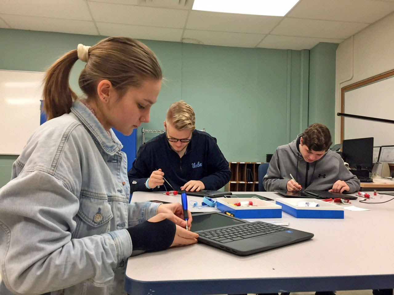 Olivia Foust, Artturi DeBlieck, and Logan Gray work on Chromebooks