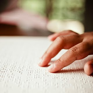 Photo of fingers reading Braille.
