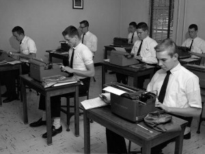 Students typing diligently on old fashioned typewriters