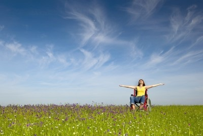 photo of woman in wheelchair showing elation with arms raised toward a clear blue sky above a field of wildflowers
