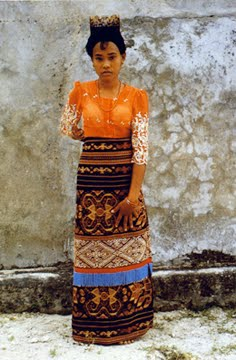Young girl in East Sumba wearing ceremonial sarong and turtle shell comb.