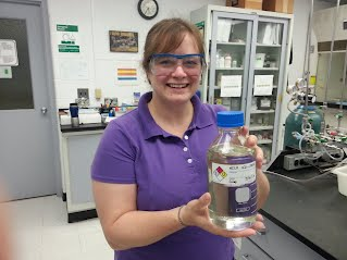 Elisha Cram a Research Engineer at UMaine FBRI Technology Research Center holding a diesel-cut of hydro-treated UMaine TDO oil Credit University of Maine Forest Bioproducts Research Institute