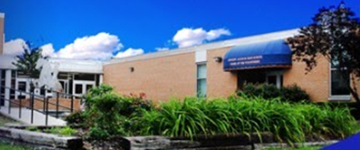 Image of Andrew Jackson High School Building blue sky and greenry