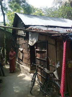 Subrata's home with his mother in the background
