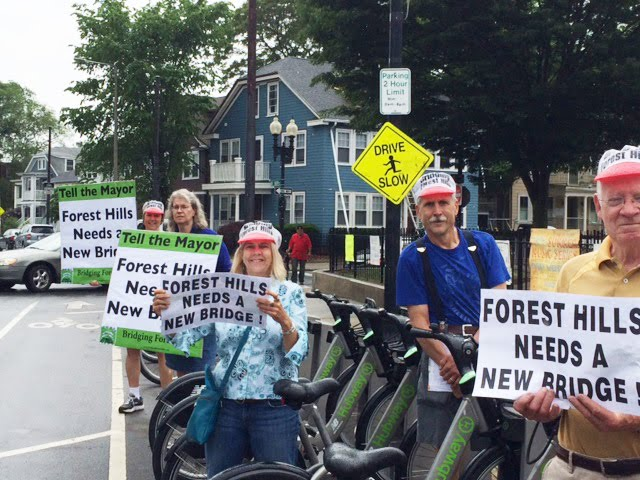 "[Bridging Forest Hills supporters in their signature BFH hats hold up signs saying: ""Tell The Mayor Forest Hills Needs A New Bridge!""]"