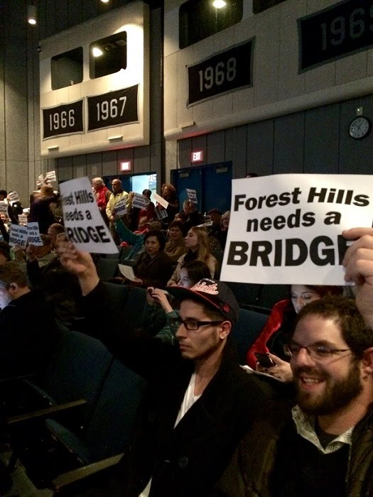 [Image: people hold up signs that say Forest Hills needs a BRIDGE. Photo by Rhea Becker.]