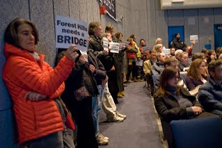 """[Image: people standing and holding up signs """"Forest Hills needs a BRIDGE."""" Photo by Laura Wulf.]"""