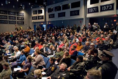 [Image: packed auditorium at English High on Jan. 21, 2015 with people holding Forest Hills Needs A Bridge signs dotting the crowd. Photo by Laura Wulf.]