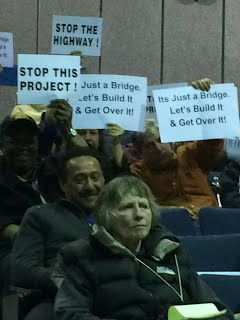 [Image: people in auditorium hold up signs that say STOP THIS PROJECT and It's a Bridge. Build It & Get Over It.]