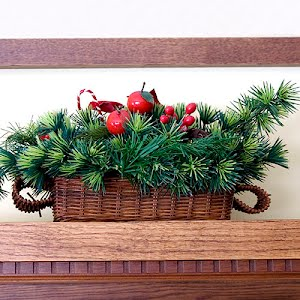 vintage wicker Christmas basket with greens and decorations