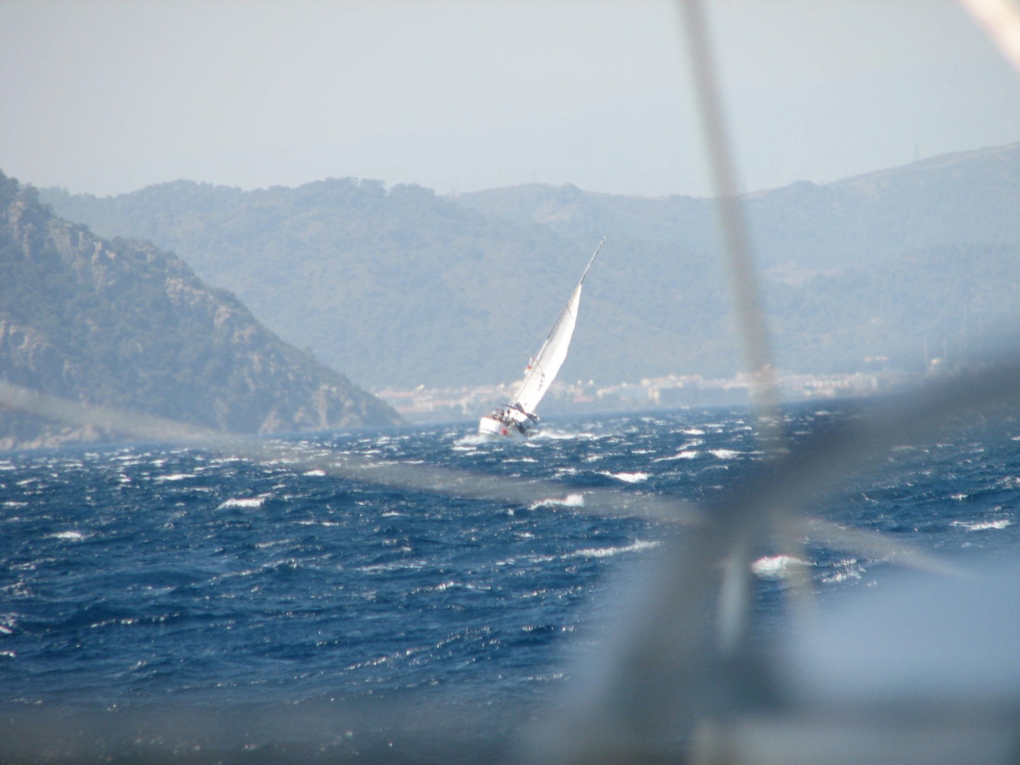 A sailboat in rough seas leaning to the right because of high winds
