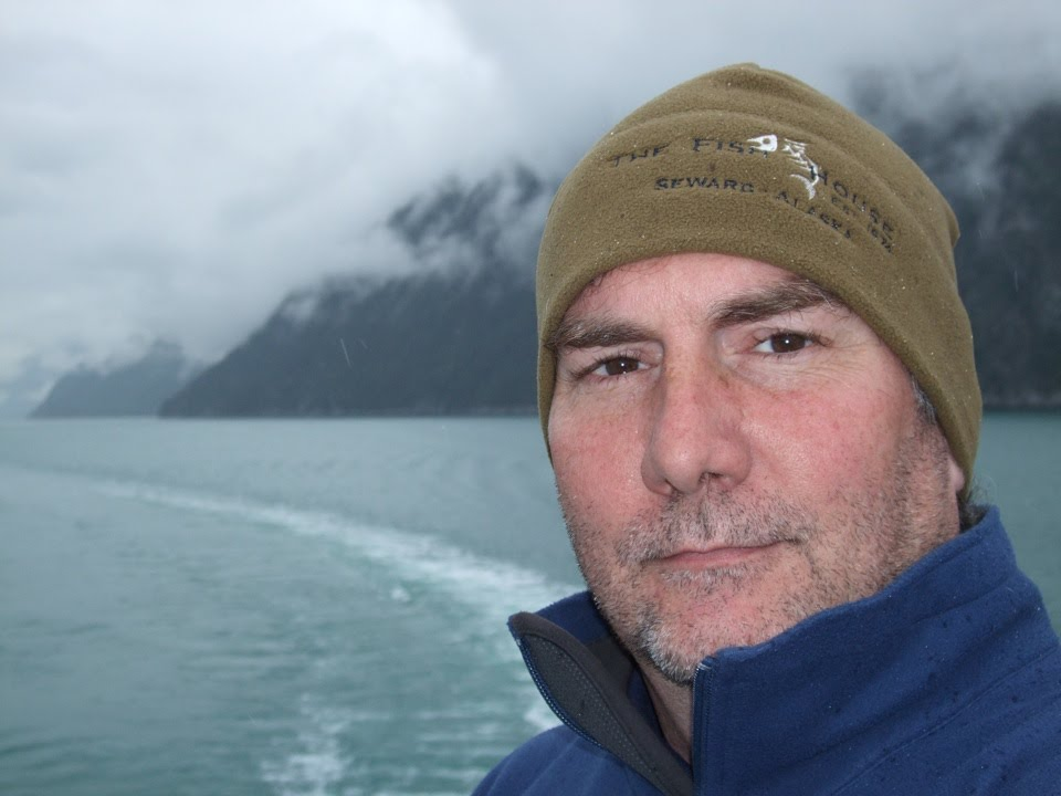 A close-up of man in a brown ski cap with the ocean and mountains in the background