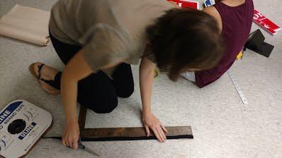 Volunteers measure and cut hook and loop material