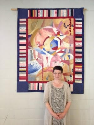 Rev. Jennie Barrington standing in front of beautiful quilt