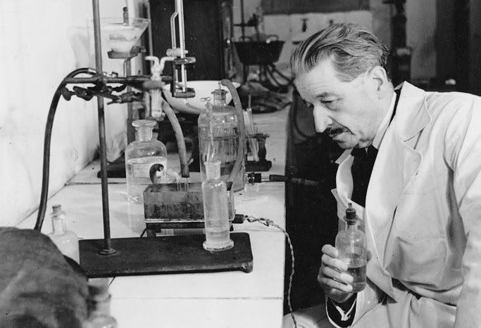 Black and white photo of Edmund Locard in an early crime lab with chemicals.