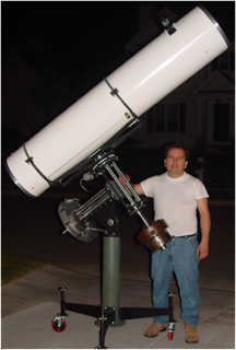Dr. Luzzio standing outside at night with a telescope.