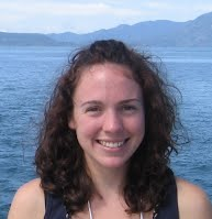 Photo of Alicia with frizzy hair in a lake in front of mountains.