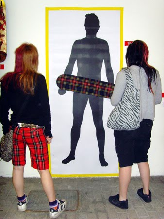 girls pose infront of art piece