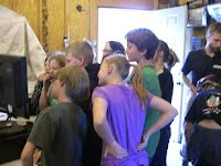 Kids crowd around the CaveSim computer to watch a classmate