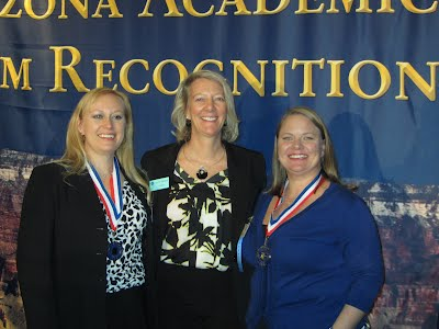 Chapter President, Cathleeen Goodell, Dean of Arts , Dr. Lee Bornstien, and VP of Leadership, Kelly Miller are posing for the camera at the Arizona Academic Team Luncheon.