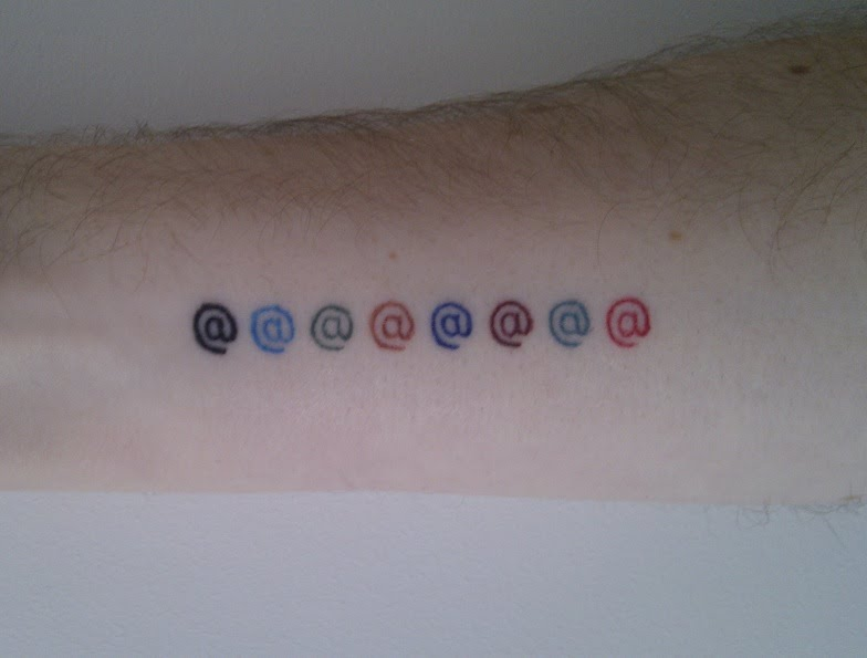 Close-up of my roguelike tattoo - a series of @ symbols