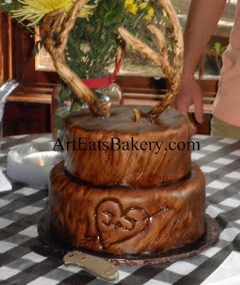 Edible deer antlers on wood grain with heart and initials carved in groom's cake