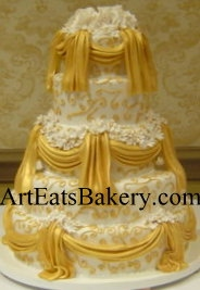 Five tier white fondant wedding cake with hand painted gold drapes, curlicues and edible sugar flowers