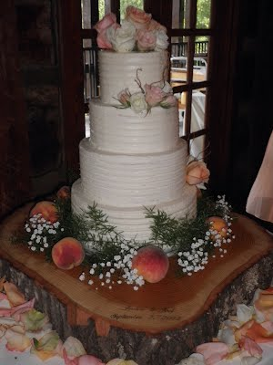 Four tier rustic butter cream wedding cake with flowers, peaches and wood slab cake stand carved with the couple's wed date