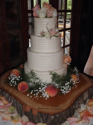 four tier rustic butter cream wedding cake with flowers peaches and wood slab cake stand - Wedding Cake Design Ideas