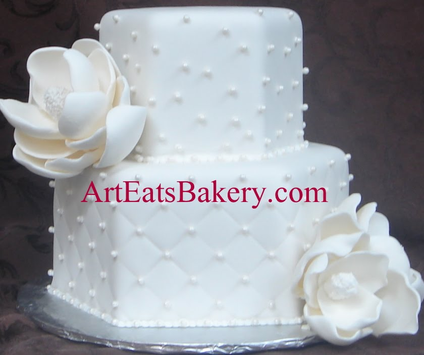 Two tier unique hexagon white fondant wedding cake with edible magnolia flowers, sugar pearls and monogram topper
