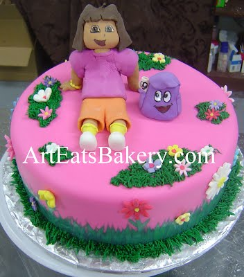 Dora The Explorer edible sugar figure and backpack pink fondant birthday cake with sugar flowers and grass