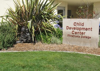 "Statue of two children reading a book under a plant.  Next to the statue, a sign reads, ""Child Development Center MiraCosta College."""