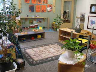 View of a toddler classroom.  In the center of the room there is a rug, shelves, and toys.  Plants are in the foreground and children's artwork is hung on the wall.