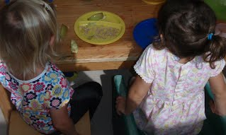 Two children sit at a table with food on plates in front of them.