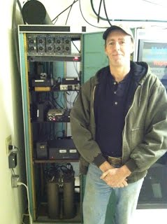 Mike Fowler (K4WAT) in front of the Mt. Mitchell 2m & 220 repeaters.