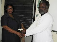 Halstead Byron, Public Relations Officer, Nevis Amateur Athletic Association hands over cheque from NACAC for sponsorship of Ivor Walters Primary School to Mrs. Jennifer Hodge, Principal Education Officer