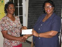 Mrs. Jennifer Hodge, Principal Education Officer, hands over cheque from NACAC for sponsorship of Ivor Walters Primary School to the Headteacher, Mrs. Ilena Mills