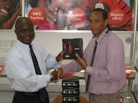 Mr. Taj Richards, Digicel Customer Care & Support officer, hands over 5 walkie-talkie capable cell phones to Mr. Wakely Daniel Vice-President NAAA