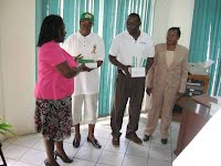 Mrs. Connor, Acting Principal Education Officer, accepts items donated by Milo representative, Joy Peets, for all athletes for the 2009 Primary Schools Championship
