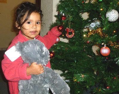 Young girl enjoying redecorating Christmas tree