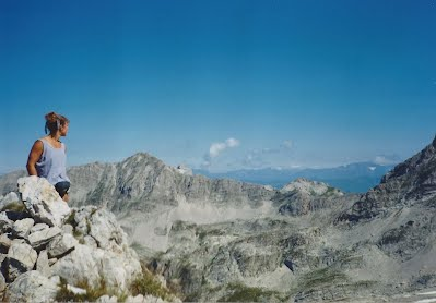 woman sitting on the top of a mountain, clear blue sky