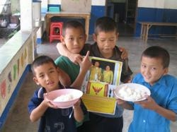 Opportunity for Poor Children boys holding picture of king and queen of Thailand