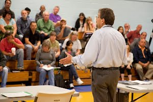A man addresses an audiences at a community meeting in New Jersey