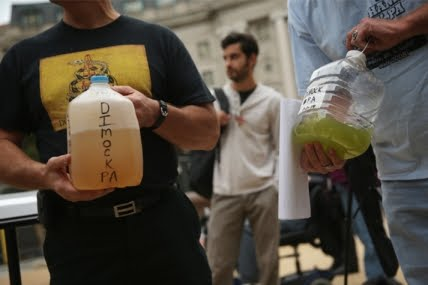 Pennsylvania residents show water samples collected from Dimock