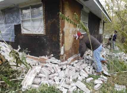 Resident examines bricks that fell from three sides of his home in Oklahoma following two earthquakes that hit the area in less than 24 hours